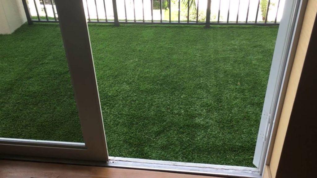 Живая зеленая трава на маленьком балконе